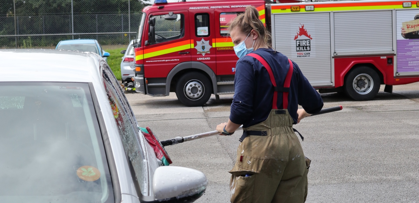Car wash header firefighter with mask on